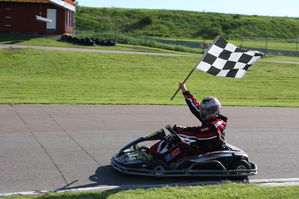 a racetrack, go-kart racer, green field, black and white checkered flag, racer raising flag, go-kart, helmet